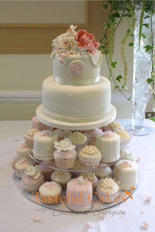 Vintage style 2 tier stacked wedding cake with cupcake and mini cake tower. whites, creams and dusky pink wedding cake.